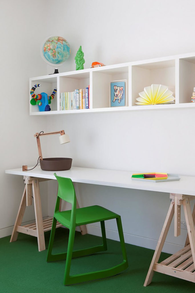 The green carpeting extends to a small study area, with a uniquely modern-rustic styled white and natural wood desk beneath a set of cubic wall-mounted shelving.