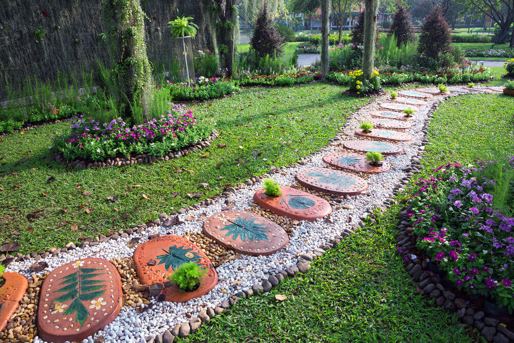 Decorative oval pavers with painted leaf designs. In every other paver is a cottony shrub planted in its hole while edging the pathway are brown, grey and white stones.