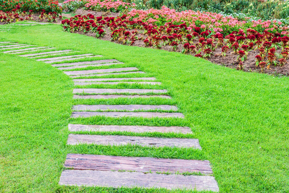 These wood pavers march in pairs to a grassy pathway. As you can see each step is bundled with a pair of elongated concrete paver designed in wood veneer.