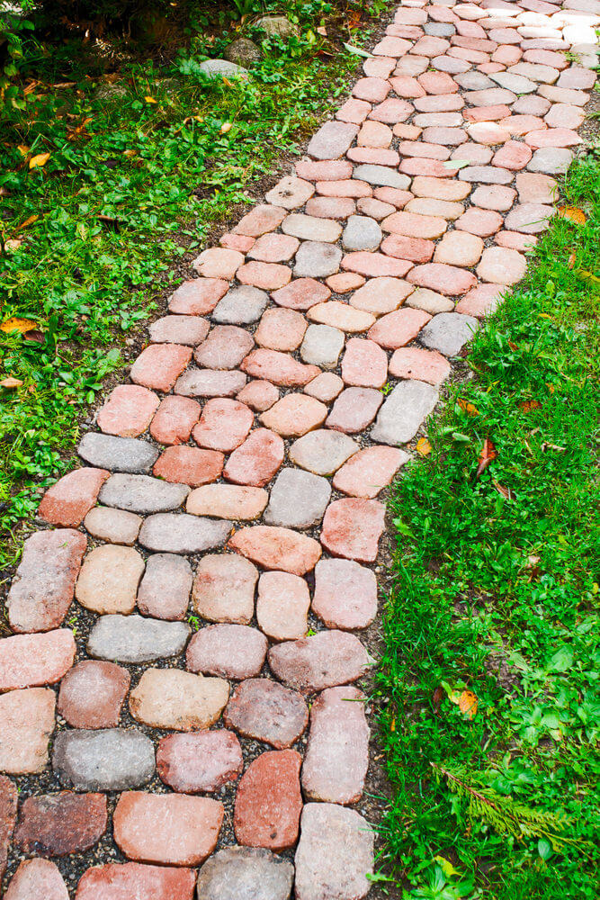 Clay brick stones shaped in ovals are laid into a pathway.