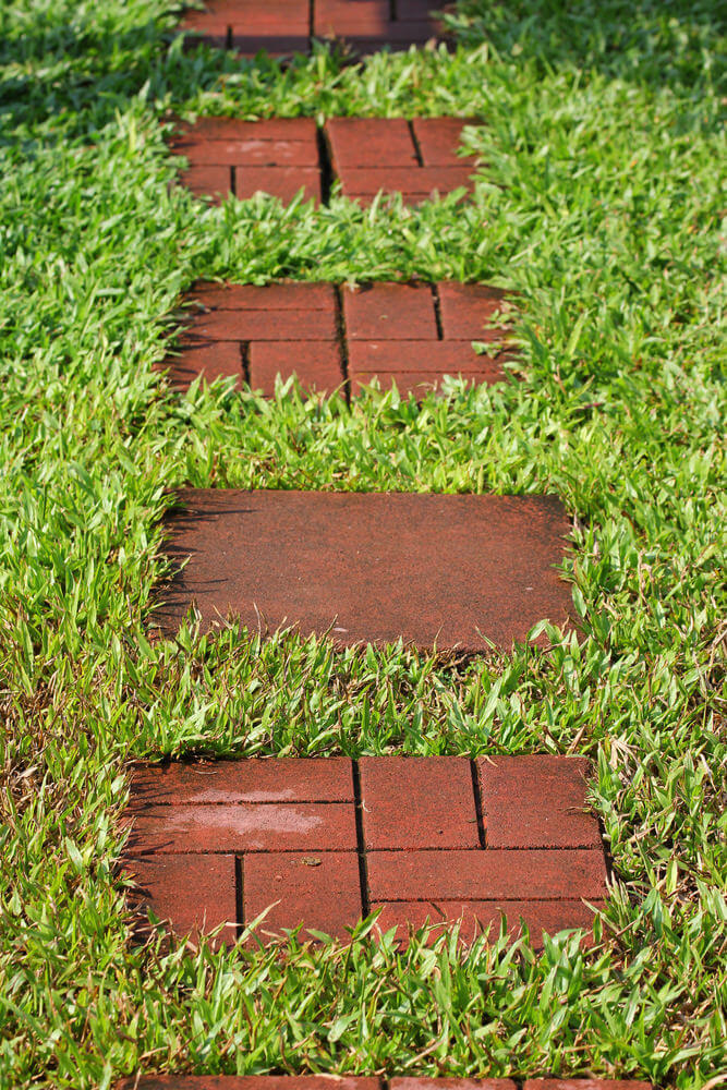 Clay brick stones arranged in an interlocking pattern are affixed in grassy ground.