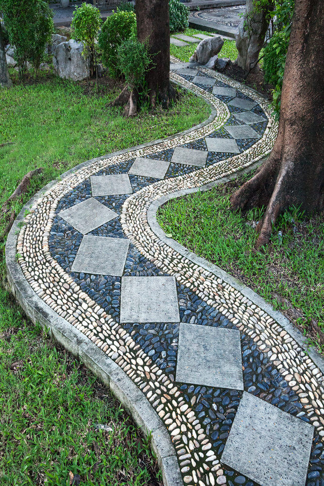 A curving pathway with diamond pavers filled with blue and white stones is  making its way