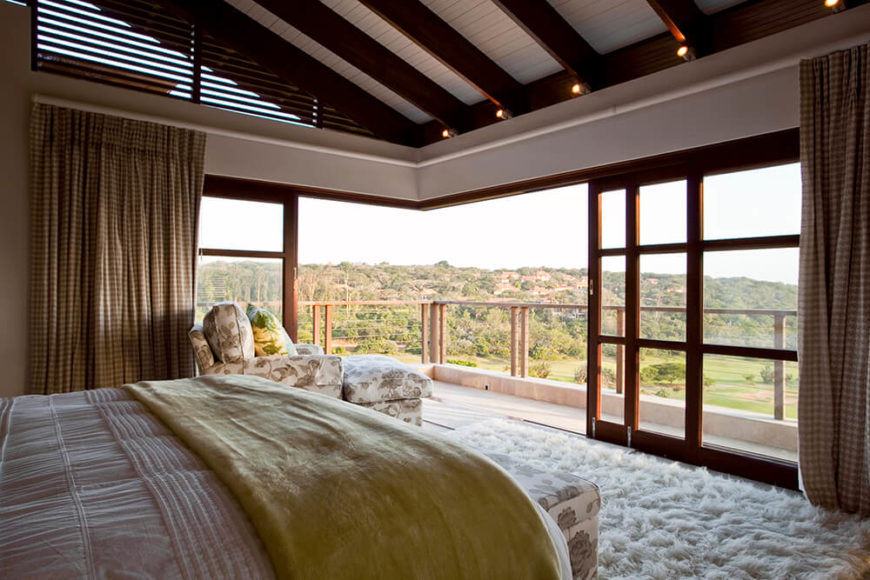 The upper level houses the master bedroom, which boasts a similarly broad opening to the outdoors. Sliding glass panels surround the room entirely, allowing for a total blurring of the line between indoors and out.