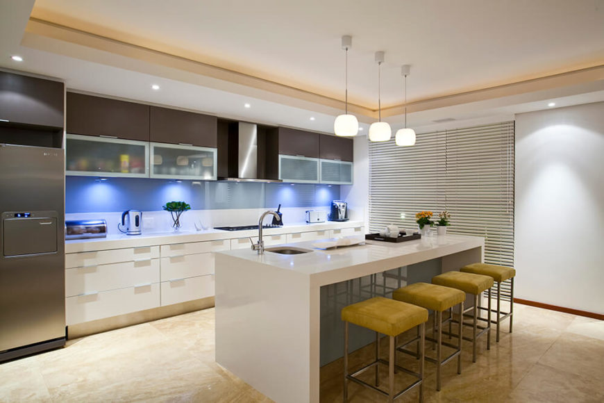 The kitchen is bordered by this large, sleek white island with a built-in sink and plenty of room for barstool dining. The blue glass backsplash is lit from within the upper level cabinetry, while modern white cupboards fill the space below.