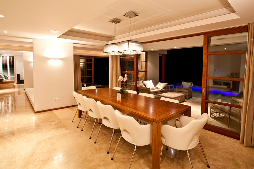 Dining area featuring a rectangle dining table with white chairs under the tray ceiling featuring a pair of modern ceiling lights.