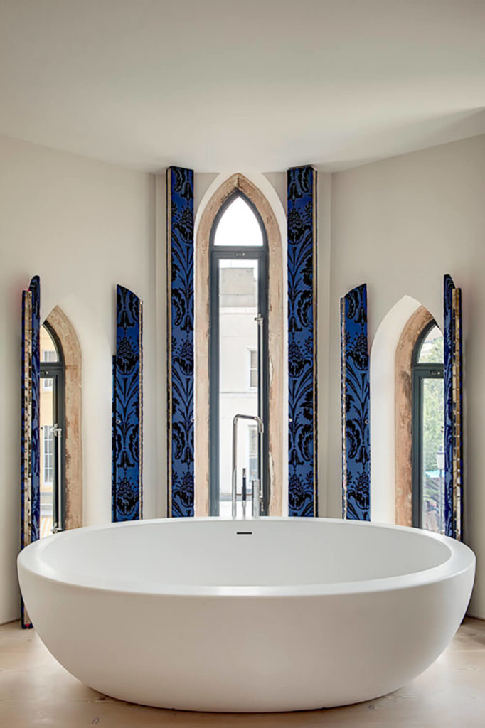 The Master Bathroom Features A Trio Of Arched Windows That Let In Plenty Of  Light,