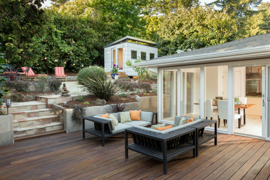 The Plain Wooden Deck Attached To The Main Home Leads Up To A Secondary  Patio And