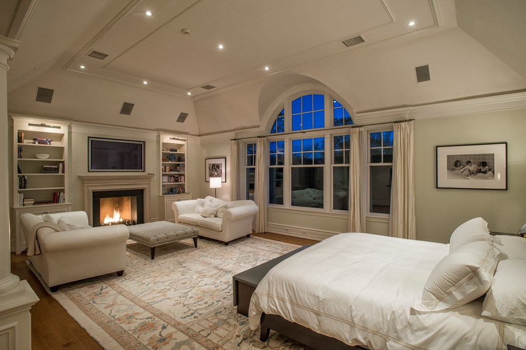A beautiful bed, armchairs to relax, and a cozy fireplace is what is striking in this bedroom.