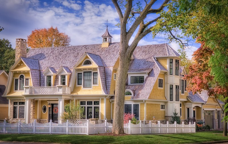 The first thing that comes to mind when I look at this traditional shingle home is how charming it looks with its white picket fence and modern farmhouse facade.