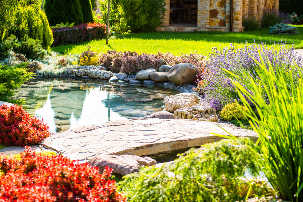 Gorgeous red bushes, lavender flowers and an arched stone bridge make this a great addition to the backyard.