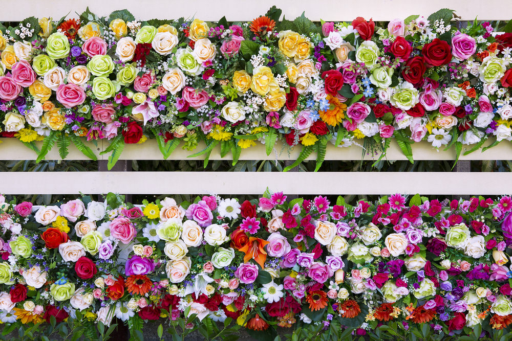 Color flooded arrangement with colorful blossoms of pink, white, red, yellow and green roses as well as other colorful blooms of daisies.