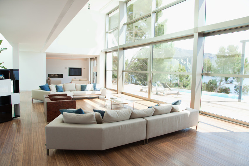 Walnut floor with a simple and plain sofa accented with a few blue pillows. Nothing more is added except from an outside view seen through a clear glass wall. This is quite spacious and relaxing.