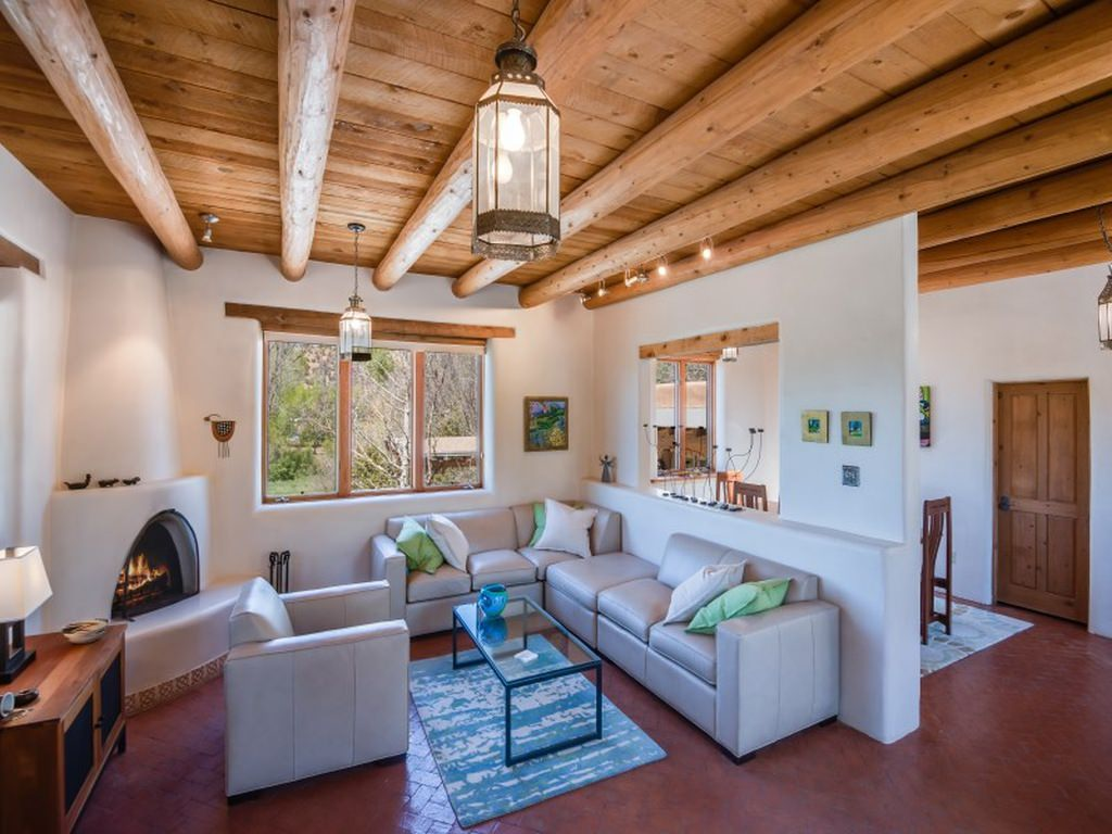 A simple designed Southwestern living room with log beams and wooden ceiling. It also features a brick patterned floor.