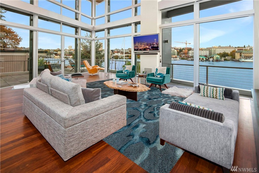 A beautifully arranged living room viewing the blue waters of Seattle. Furniture is uniformly patterned to match with the blue themed surroundings outside the clear glass wall. It is more of a modern interior accented with a few bright colored seats and pillows.