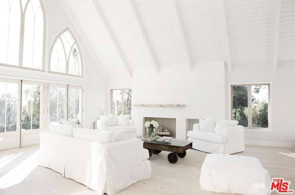 A very majestic white living room with a wooden wheeled center table highlighting its natural brown shade.