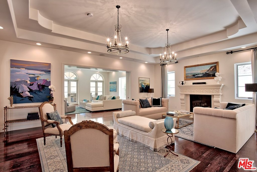 dazzling white furniture and wall to ceiling painting await in the living room contrasting colors - Mansion Living Room