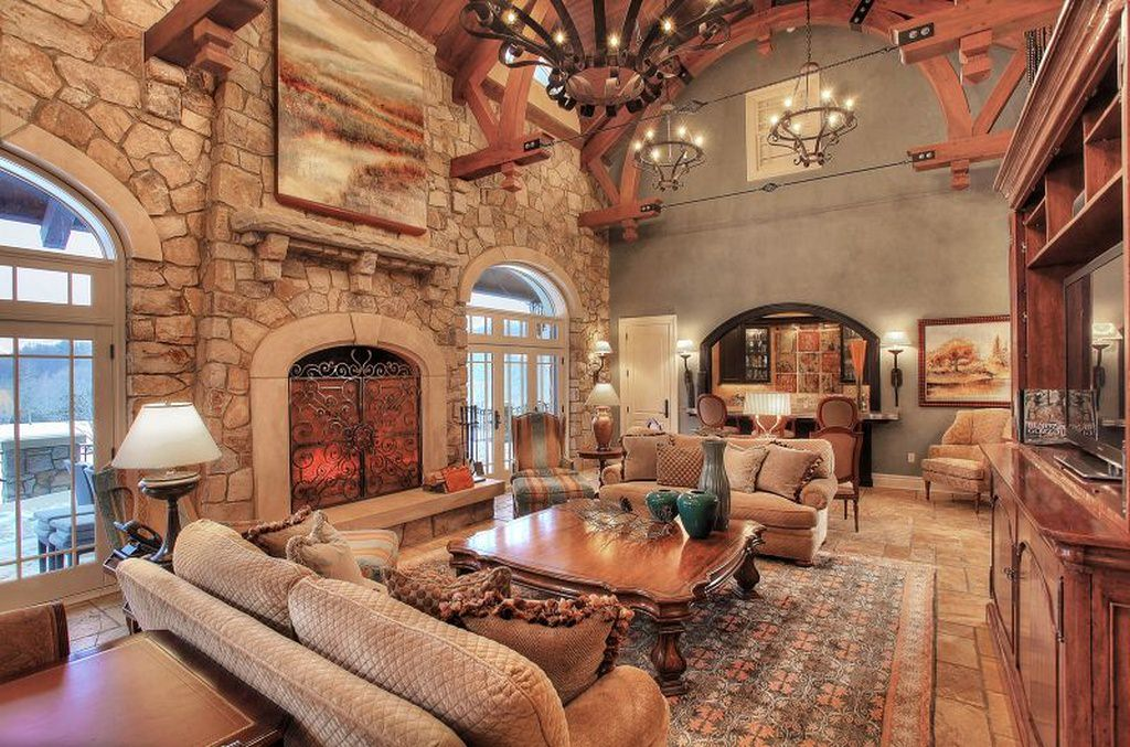 A rustic and traditional inspired interior with bold and detailed wood and stone designs. A few carvings on the furniture are visible and a traditional sofa, lampshade, chandelier and fireplace add to the old and classy touch.