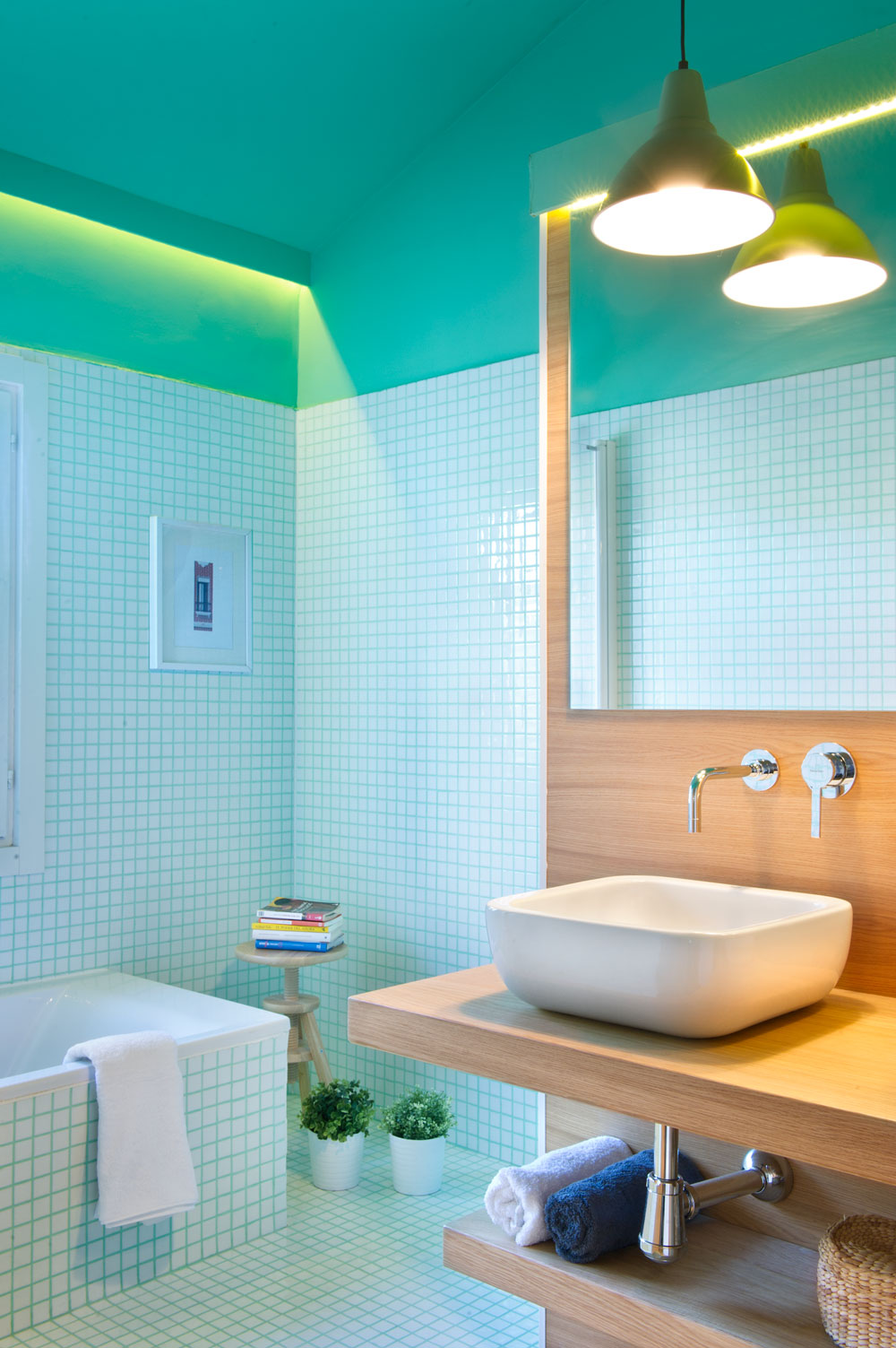 Tiny pieces of tiles are vividly attached to form an entire bathroom flooring and wall. A comfy bath tub is working well, a functional wooden stool for your books and under sink shelf for toiletries and towels are installed for your convenience.