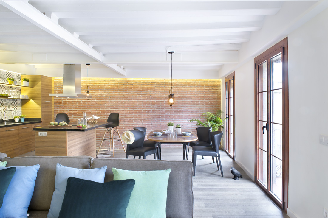 Beams on the ceiling are painted in white to match up with the wall paint while the color itself is a bright add up to the areas lighting. Grey tone flooring and sofa give it the cool touch of industrial design.