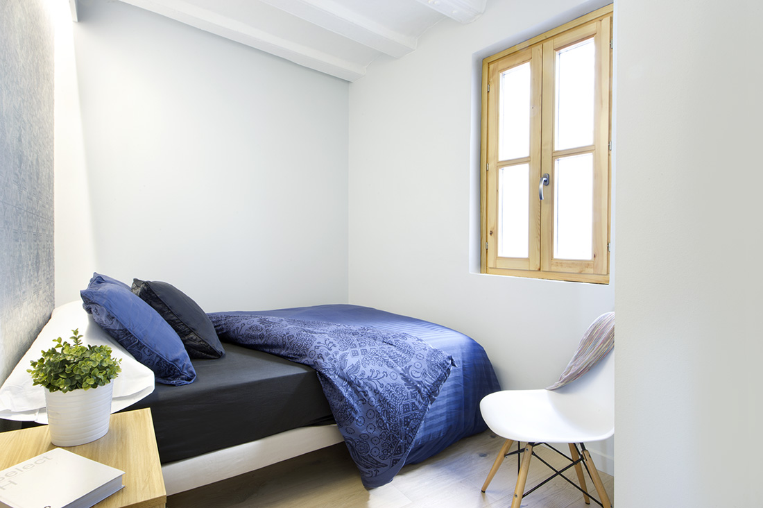 A small yet free moving bedroom with a soft mattress with a dark and bright blue covers and pillow. It also has an average sized window for ventilation and natural lighting.