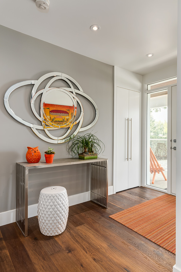 A contemporary designed entry way with decorative wooden desk and porcelain vase underneath a sleek and uniquely designed wall mount mirror. The wooden floor texture does match with the orange shade floor rug and a few desk mounted decorations.