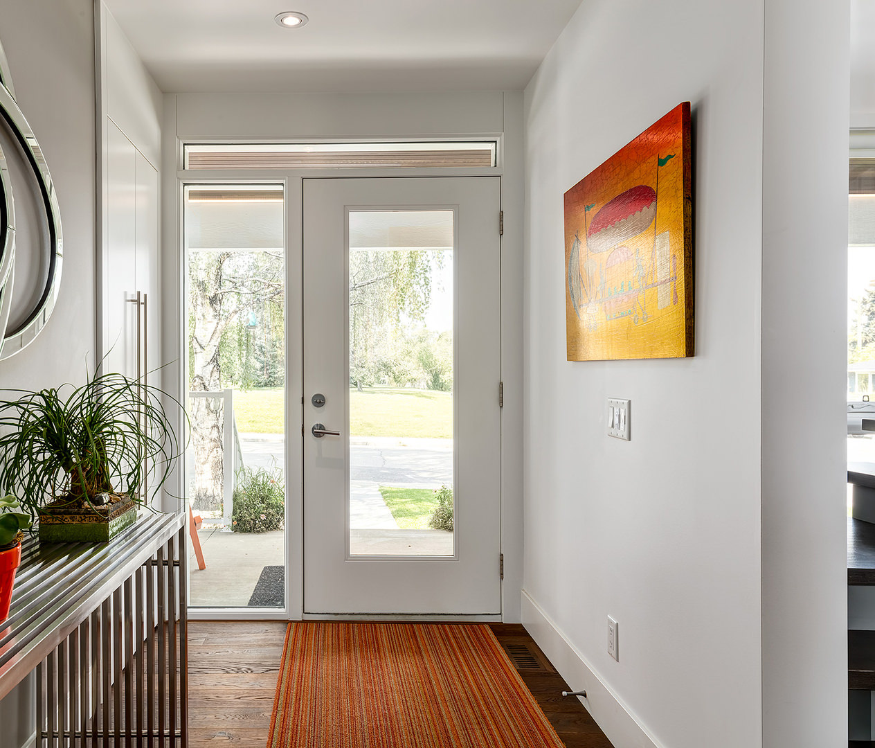 The warm grey tone walls are neutralized by the bright colored floor rug and wall painting. Also, the natural lighting from the outside shines inside through the glass door.