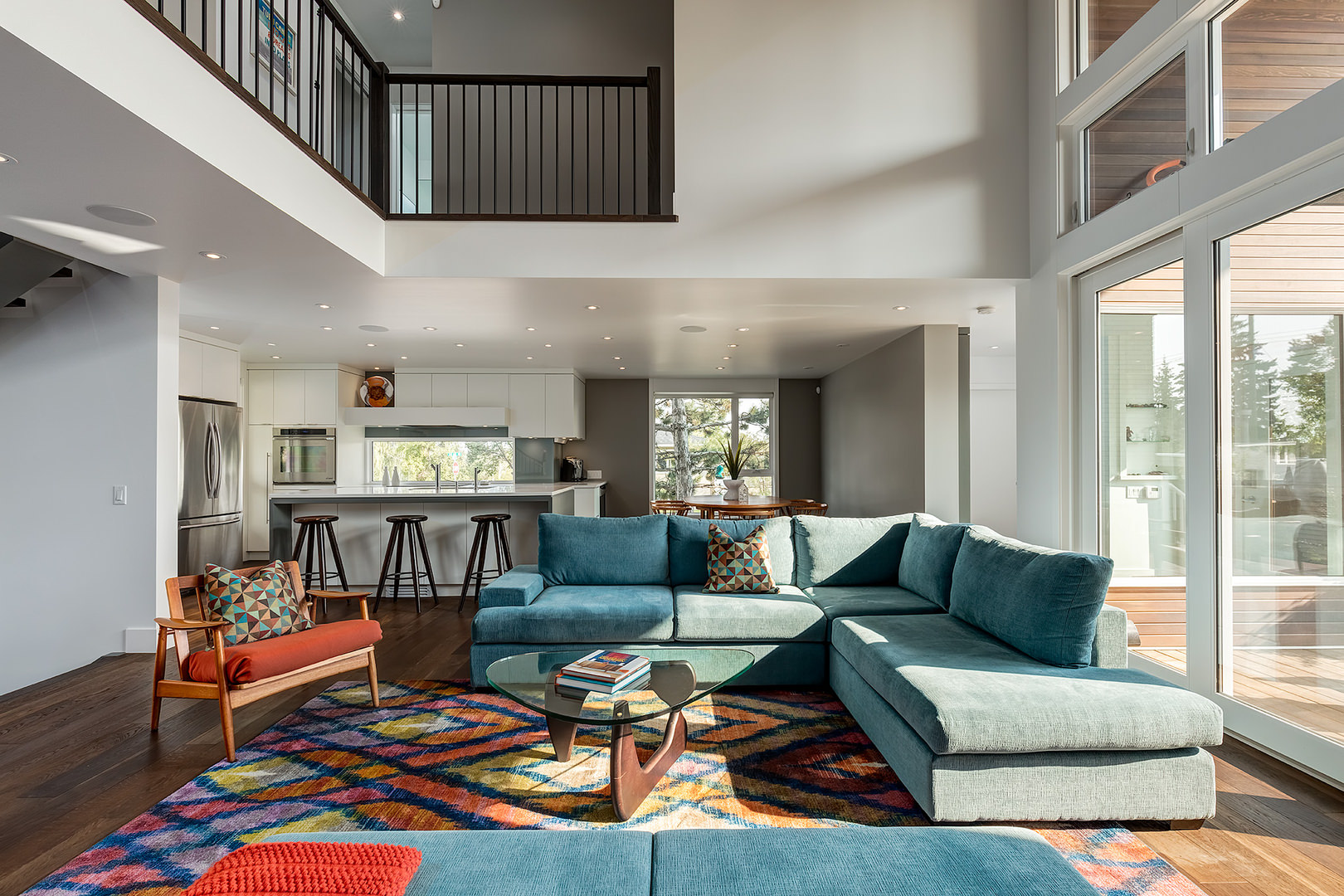 The central living space extends all the way up to the second floor with wooden railings taking a peek over the picture.