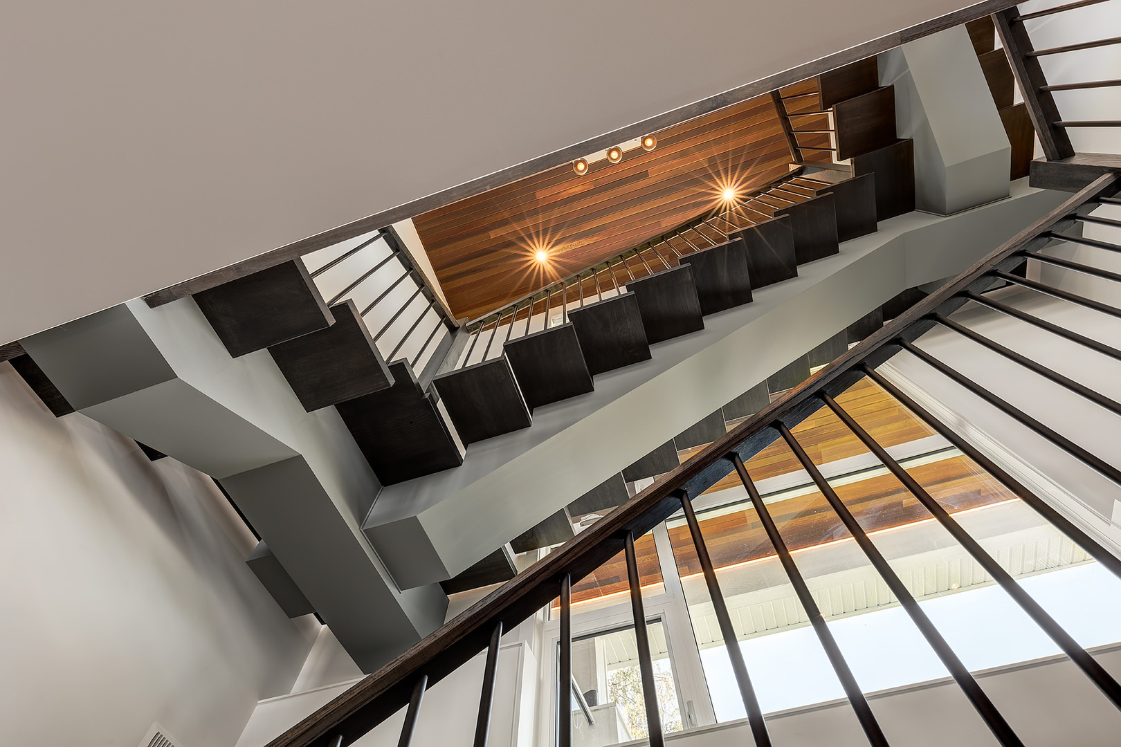 This is the view of the staircase from the lower level seeing it crawling on the side walls up to the second floor. The ceiling is made with a wooden texture.