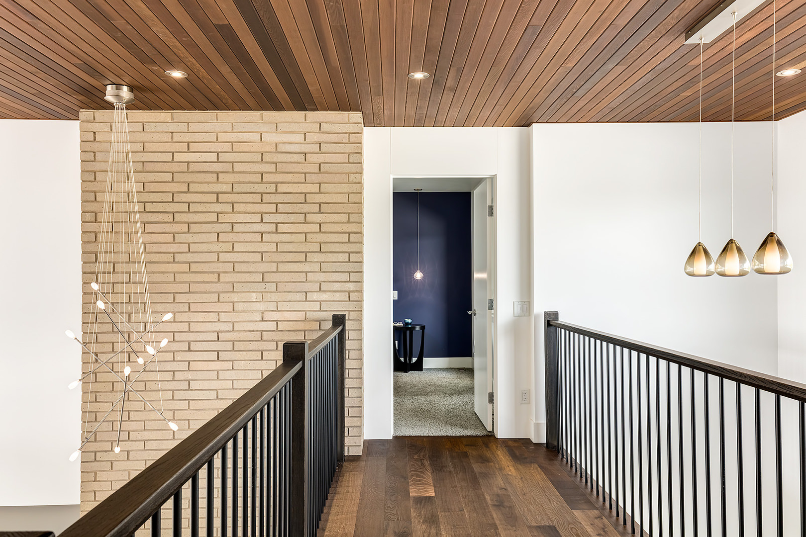 The short wooden bridge way connecting the staircase to the other rooms. The railings are made of hardwood while the floor is covered with wood planks.