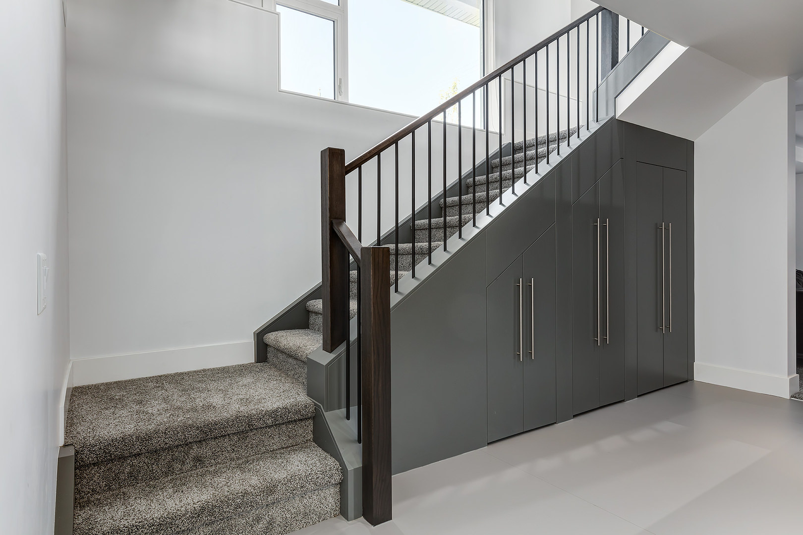 This functional staircase is carpeted with textured grey rug with wooden railings on the side and steel cabinet storage underneath.