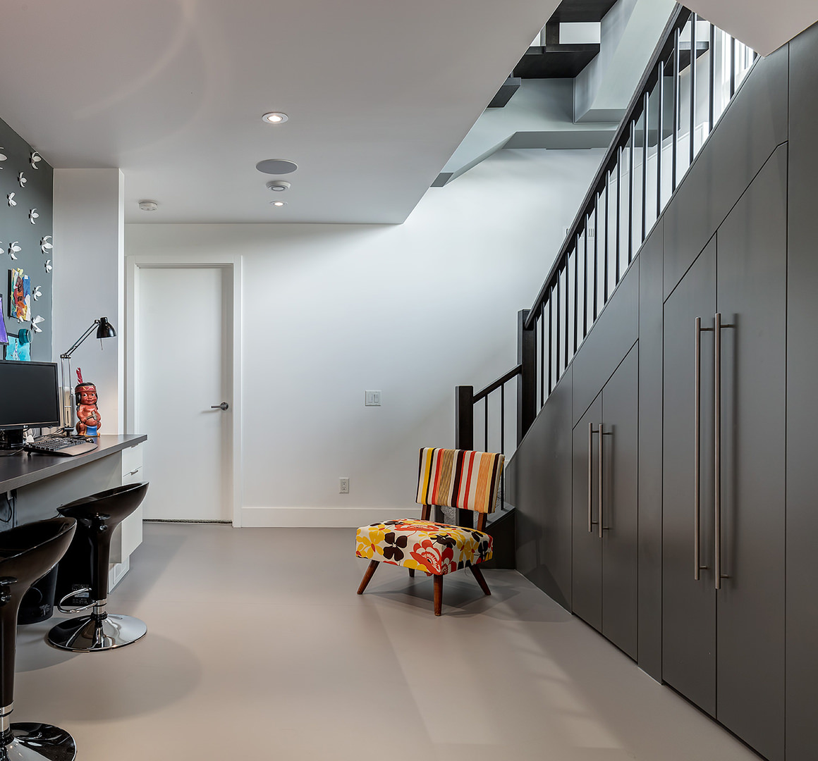 Facing the staircase under the steel cabinet is an IT corner where computers are set and gadgets are located. The furnishing and wall is covered with black, grey tone coating and white stucco while the floral cushioned seat stands decoratively on the staircase side.