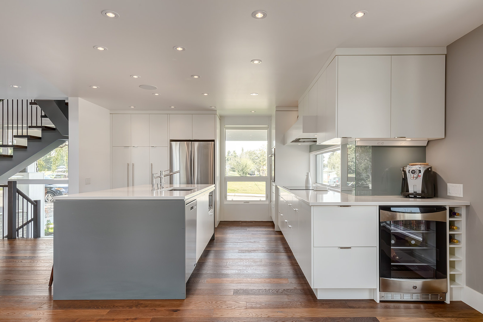 A contemporary designed kitchen that is very minimalist on its own version, no other clutters and decorative accents added aside from the white colored vanities, wooden floor and glass window. Everything is concealed in functional storage cabinets on the floor and ceiling.