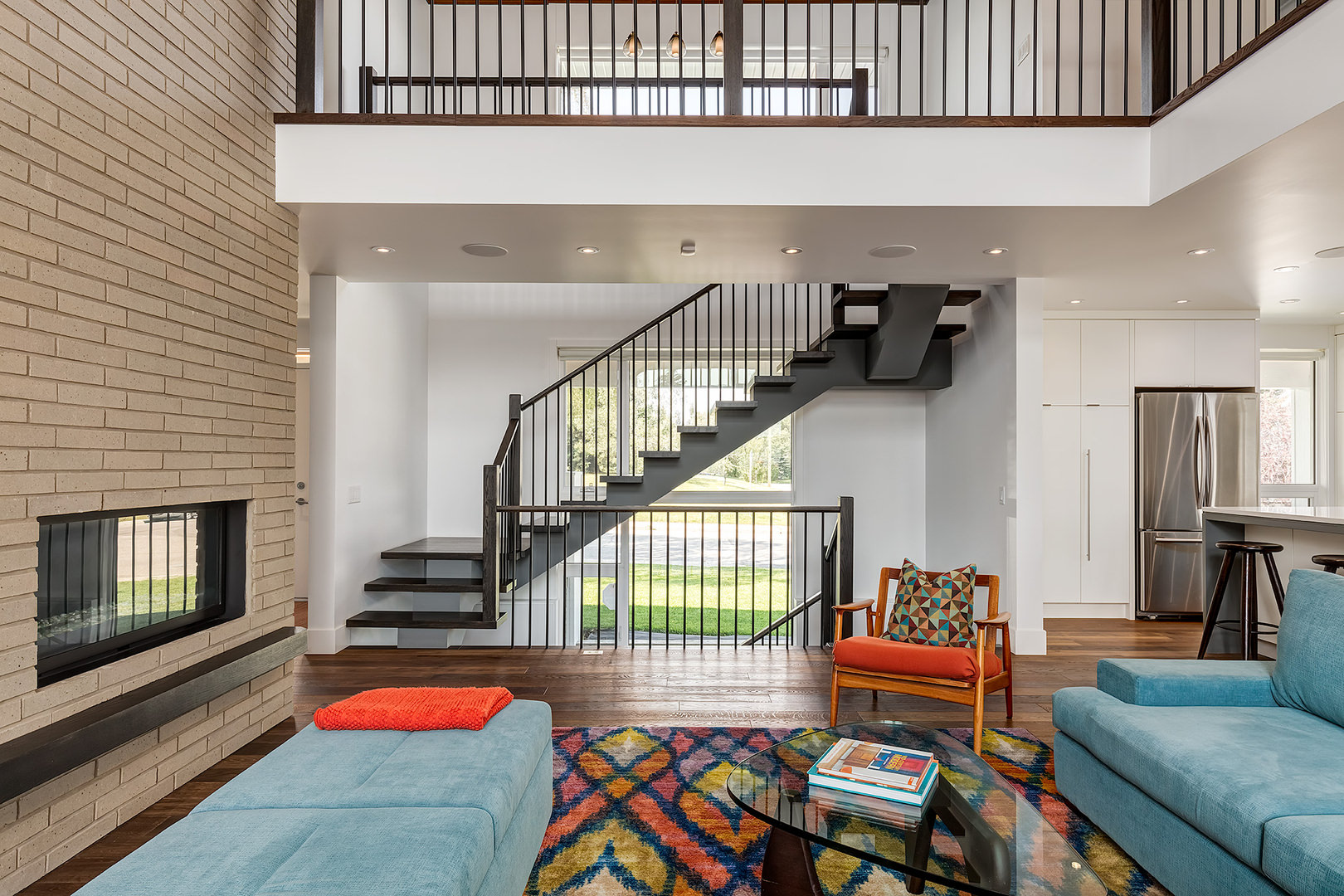 Right next to the living area is a staircase that leads to the upper and lower levels. Not to mention the brick stone wall with a fire place, which extends from the main floor up to the second level.