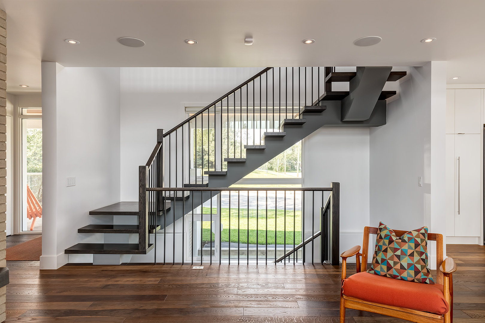 The staircase made of hardwood steps and railing is simple but stylish in its form. This could be considered a traditional wooden staircase retouched to a contemporary style.