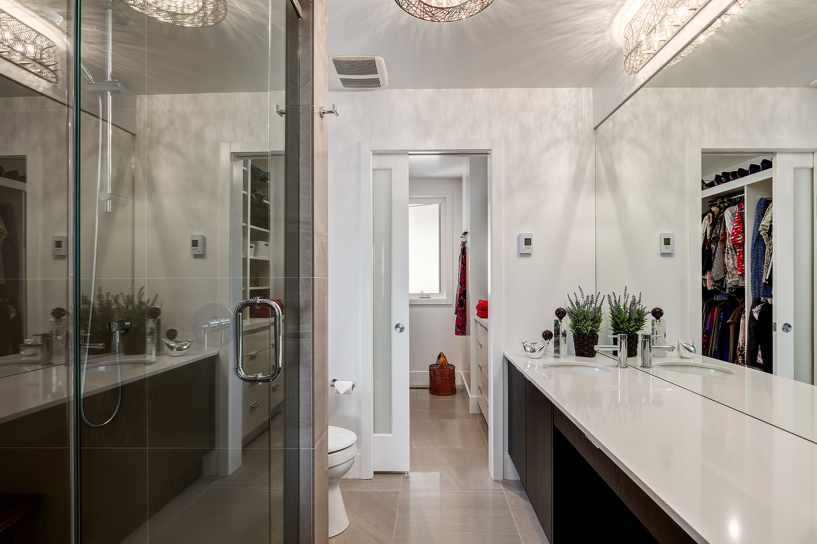 This bathroom is finished with porcelain counter top and a glass shower barrier. A few fixtures are also there like the toilet bowl, mirror and faucets. Moreover, the floor is covered with tan colored tiles extending up to the bedroom floor.