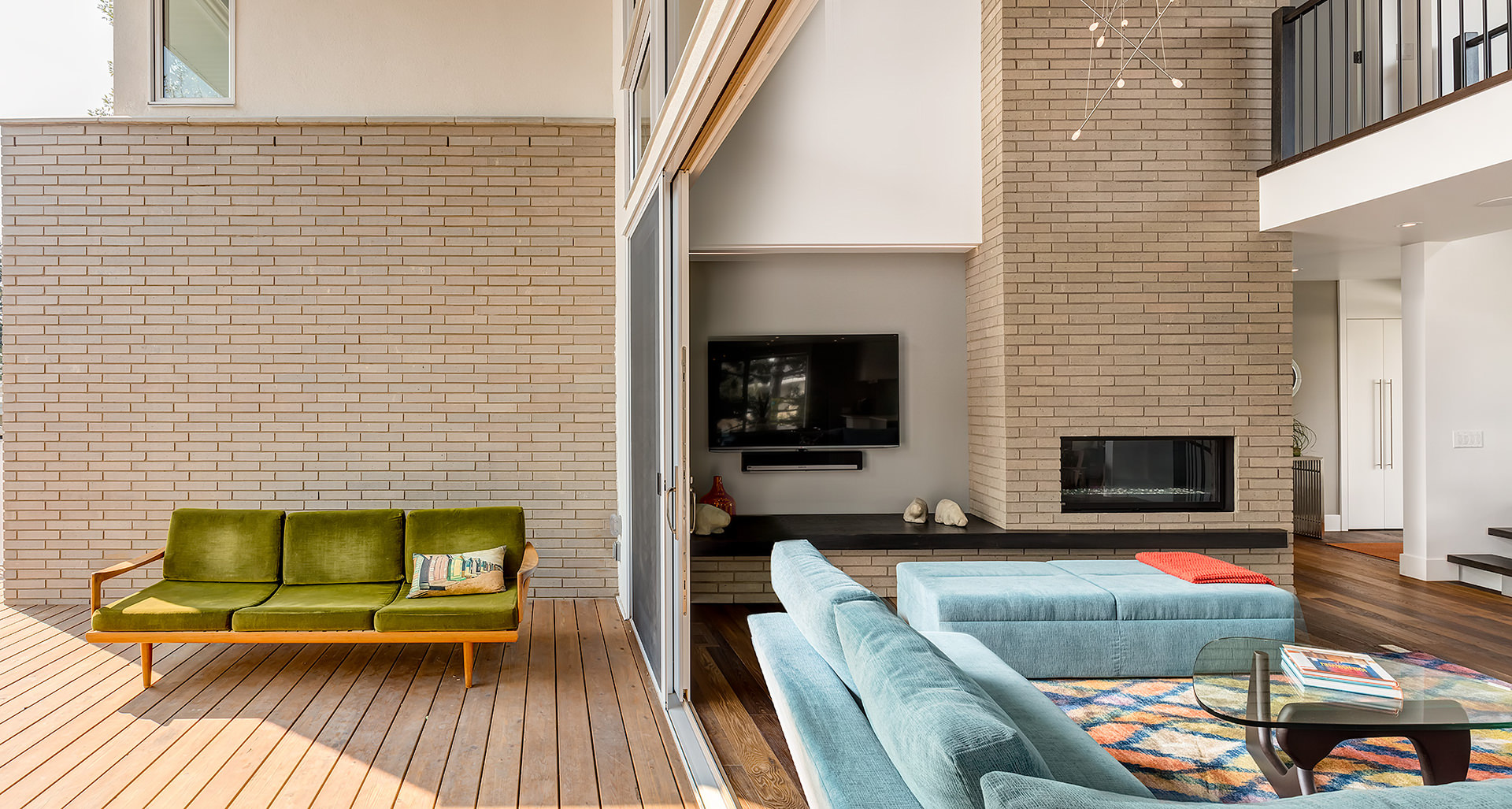 The wide entrance of this house provides an open floor concept connecting the outside porch to the living area when open. The brick wall and tongue and groove cedar floor give it a traditional yet contemporary look.