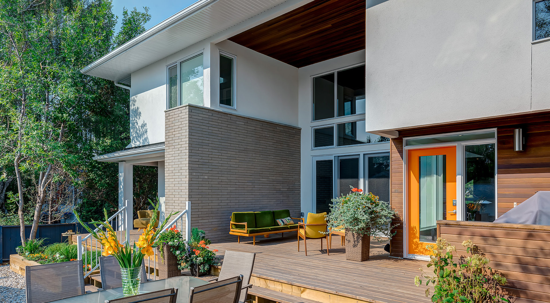 The outside porch and patio view of this house. These feature the wooden wall and flooring with the twist on the brick wall designed on the half side. Flowers and greenery are infused to provide a natural and refreshing site.