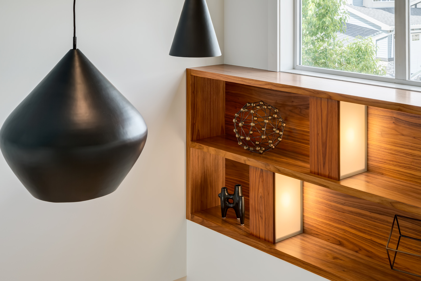 Contemporary lighting fixtures pair with natural wood and recessed shelf lighting.