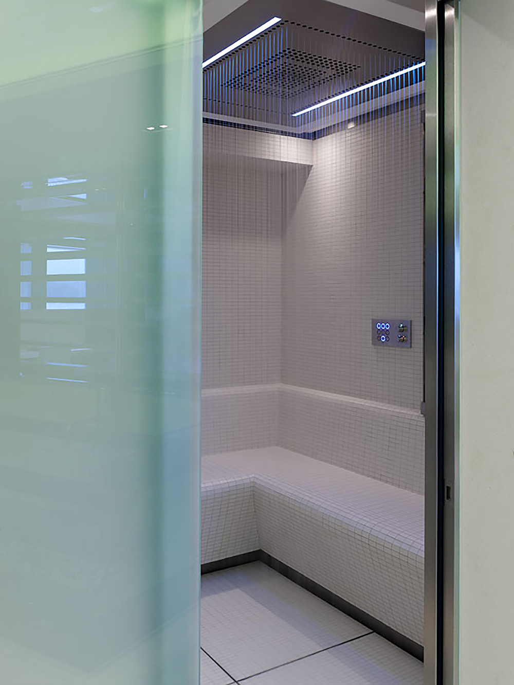 Hot and cold rain shower with pure white mosaic bath room wall bench and wall. The floor is covered with wide scale white tiles.