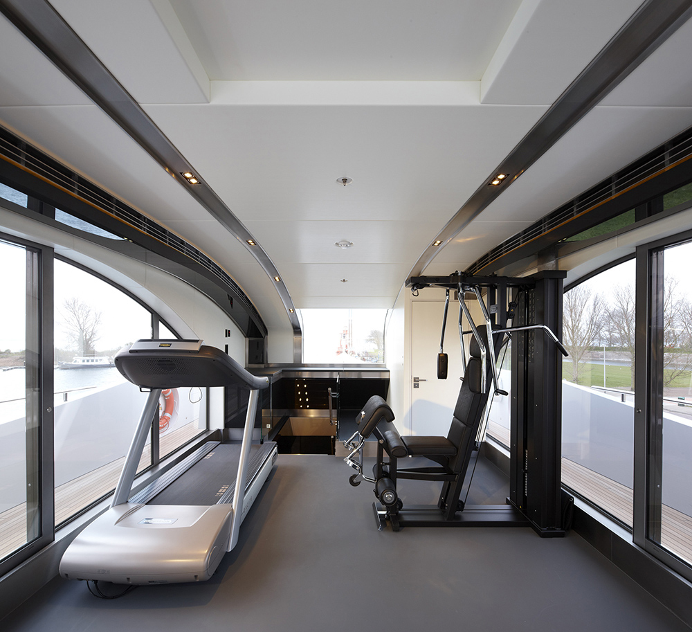 This is the technogym with sets of high tech gym equipment like the thread mill. The flooring is a smooth grey colored finish while the glass walls provide natural lighting as well as an open view of the outside. This one is located on the yacht's sun deck.