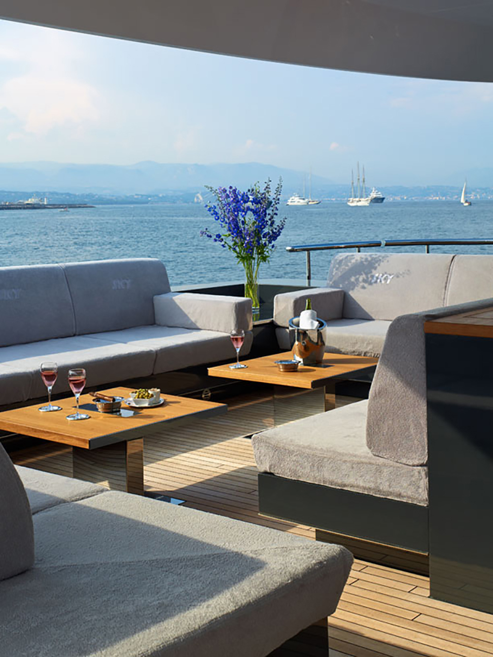 This is the open space patio designed with wood flooring and tables. Around it are the cushioned grey sofa. By having these, you can freely enjoy a glass of wine while savoring the coolness and stillness of the ocean.
