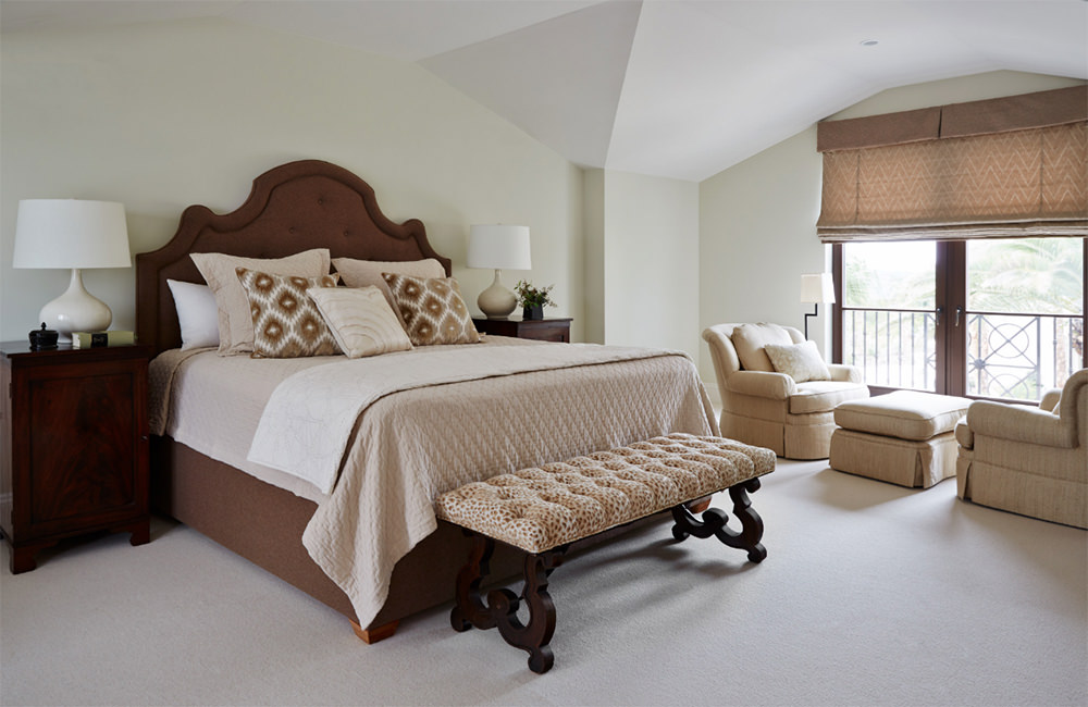 The perfect example of a warm yet bright contemporary bedroom design. The color tones are within the scale of light to dark brown added with cream and pure white tones. Textures are also adorned in the bed sheets and simple skirted curtain, while the wide wooden framed glass door allows natural light to set in.