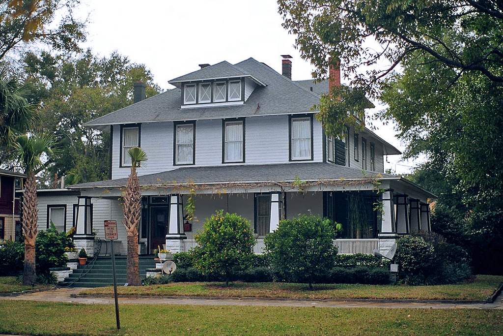 Large gray American foursquare home with porch extending along 2 sides of the home.