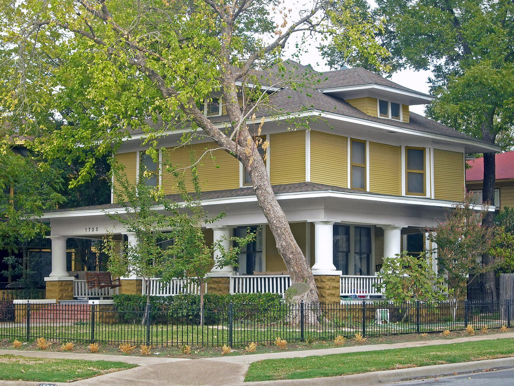 Mustard yellow and white foursquare with wood exterior.