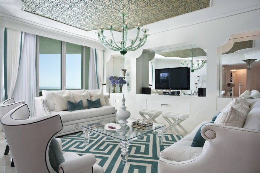 A compact yet stylish living room with nicely set up white furniture including sofas, seats and white cabinets. Curtains and walls are also white, while patterns accent the floor rug, throw pillows and the ceiling.