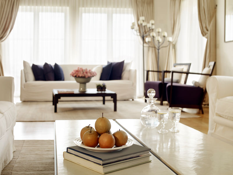The light cream sofa matches the brown toned flooring, rugs and curtains in the rest of the living area.