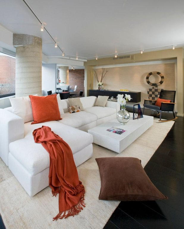 Cream, white, and light and dark brown shades combine. The orange pillow and cloth provide a contrast in tone. But it's the white sofa set and center table that stand out.