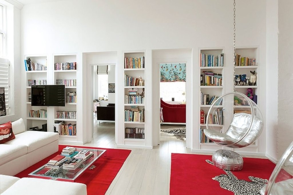 The white sofa, bookshelves, walls, floor and ceiling are highlighted the red floor rugs with leopard prints. The fashionable hanging round chair sparkles with silver cushions.