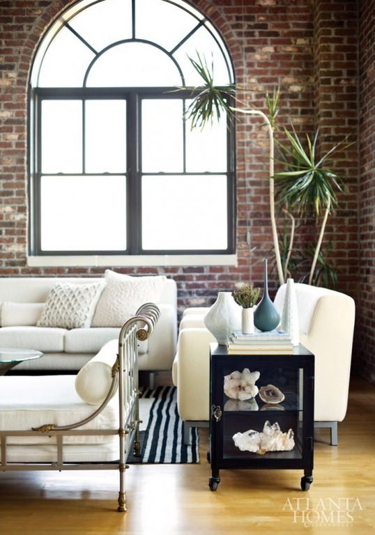 This is quite a rugged one, almost industrial with the rough textured brick walls holding an arched glass window. The white sofa set and bench with white bolster pillow add a welcome note of domesticity.