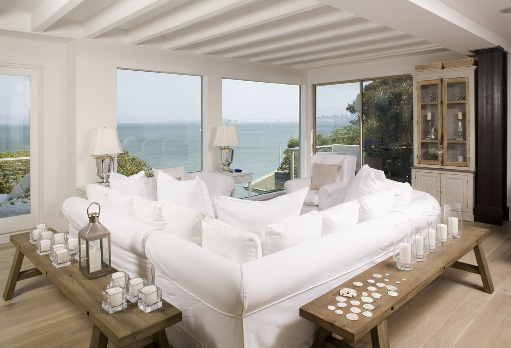 A living room in a beach house has to be as cool as the beach. The rugged wooden flooring and benches are topped with candles and frame the sofa, which is covered with clean white covers and pillows.